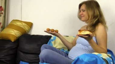 Hungry pregnant woman make decision what to eat. Bun or cakes. — Stock Video