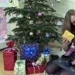 Smiling woman show her lovely baby gift box near Christmas tree — Wideo stockowe #72877243