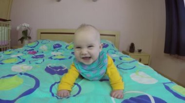 Cheerful newborn baby smile and laugh lie on belly on bed. 4K — Stock Video