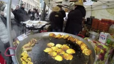 Steel pan with pancakes bake and people near outdoor kitchen — Stock Video