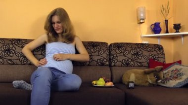 Pregnant woman sit on couch and regulate special trousers strap — Stock Video
