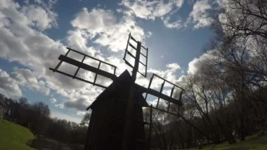 Wooden retro mill silhouette on blue cloudy sky. Timelapse. 4K — Stock Video