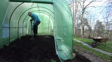 Man work hard with shovel and dig compost in greenhouse. — Stock Video