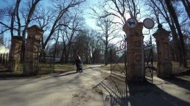 Mother with blue stroller walk retro park gate in spring. 4K — Vídeo de stock