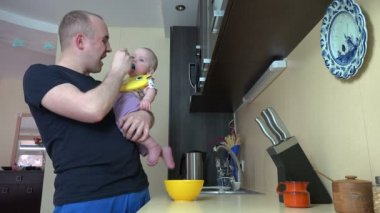Father talk with baby daughter and feed with mash in spoon. 4K — Stock Video