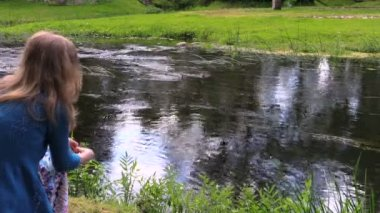 Girl sit by stream, throwing crumb duck family sunny summer day — Stock Video