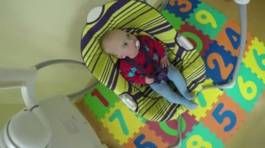 Baby boy or girl sway in colorful swing at home. 4K — Wideo stockowe