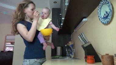 Mamma mata barn i köket. Moderskap baby vård i hemmet. — Stockvideo