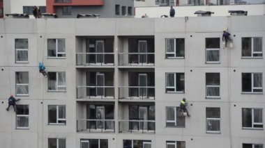 Risky construction site work. High wall insulation hang on rope — Stock Video