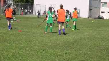 Young schoolgirls with skirts play field hockey game.4K — Video Stock