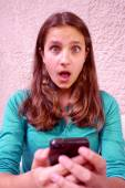Teenage girl surprised at what she sees on her cellphone — Stock Photo