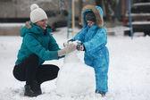Family sculpts snowman — Stock Photo