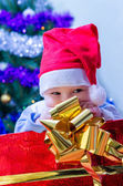 Kid under the tree a gift for the new year — Stock Photo