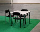 Tavolo bianco e tre sedie neri — Foto Stock