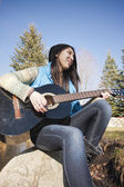Sitting on a rock playing guitar. — Stock Photo