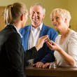 Reception - Guests check in a hotel — Stock Photo #68385113