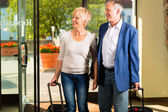 Senior married couple arriving at Hotel — Stock Photo