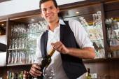 Barman standing behind bar — Stock Photo