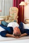Senior man lying on the bed — Stockfoto