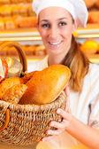 Female baker selling bread — Foto de Stock