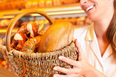 Female baker selling bread — Stock Photo