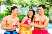 Asian friends drinking cocktails at pool — Stock Photo