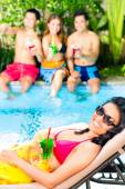 Asian friends partying at pool party — Stock Photo