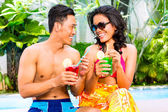 Asian couple drinking  cocktails at pool — Stock Photo
