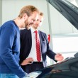 Young man and seller  in car dealership — Stock Photo #69227225