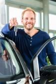 Молодой человек с авто в автосалон — Стоковое фото