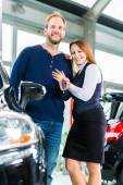 Couple with auto in car dealership — Foto Stock