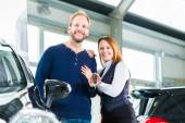 Couple with auto in car dealership — Foto de Stock