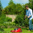 Man is mowing the lawn in summer — Stock Photo #69306185