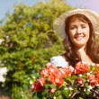 Woman in summer garden with flowers — Stock Photo #69306297