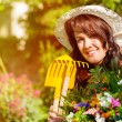 Woman in summer garden with flowers — Stock Photo #69306403
