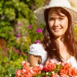 Woman in summer garden with flowers — Stock Photo #69306513