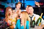 People in club or bar drinking champagne — Stock Photo