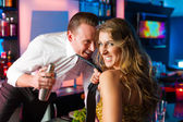 Woman dragging barkeeper in club or bar — Stock Photo