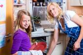 Housewife and daughter doing dishes with dishwasher — ストック写真