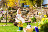 Girl on Easter egg hunt with eggs — Stock Photo