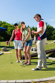 People playing miniature golf outdoors — ストック写真