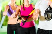 People in sport gym on suspension trainer — Stock Photo
