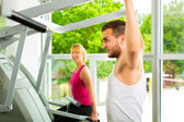 People in sport gym on the fitness machine — Stock Photo