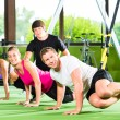 People in sport gym on suspension trainer — Stok fotoğraf #69630149