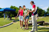 People playing miniature golf outdoors — Stock Photo