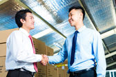 Businesspeople in warehouse have a deal — Stock Photo
