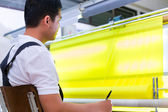 Asian worker controls fabrics — Stock Photo