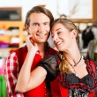 Couple is trying Dirndl or Lederhosen in a shop — Stock Photo #71689539