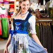 Woman is trying Tracht or dirndl in a shop — Stock Photo #71689521