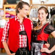 Couple is trying Dirndl or Lederhosen in a shop — Stock Photo #71689599